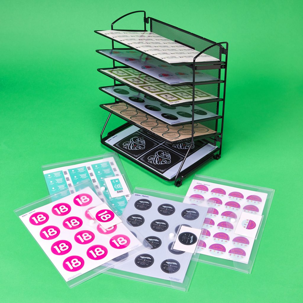 A wire file rack is repurposed to store and organize sheet labels.