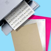A printer showing address labels being printed on Avery blank labels by the sheet are available in 25 materials.